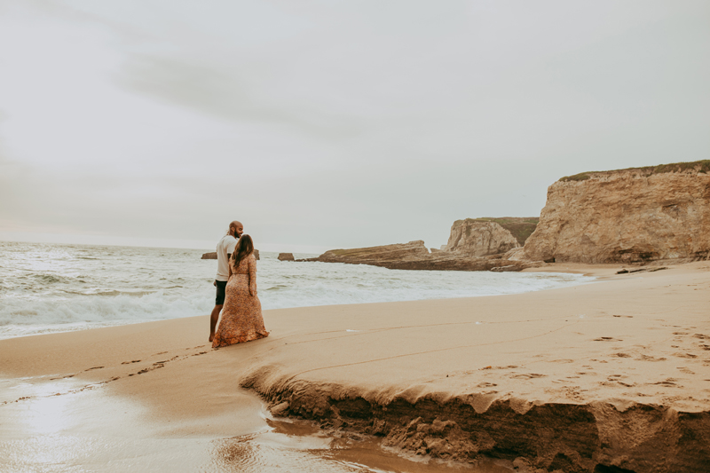 Maternity Photography, wide angle shot of couple walking on the beach