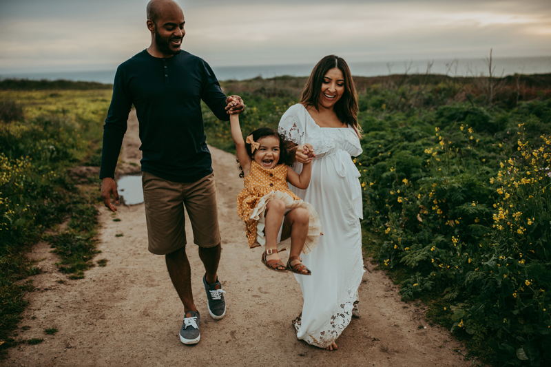 Maternity Photography, husband and wife swinging daughter between them by the arms