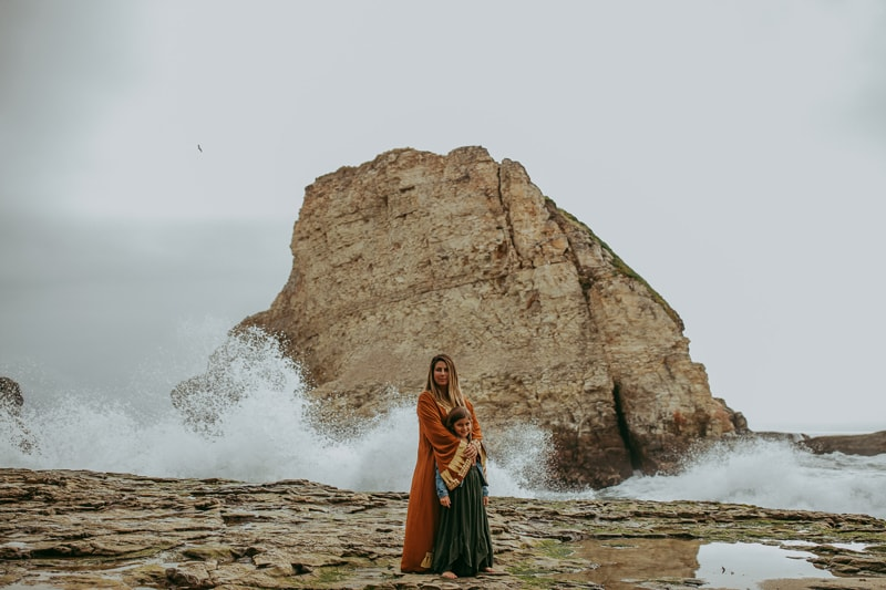 Maternity Photography, mother and daughter standing in front of a wave breaking on rocks