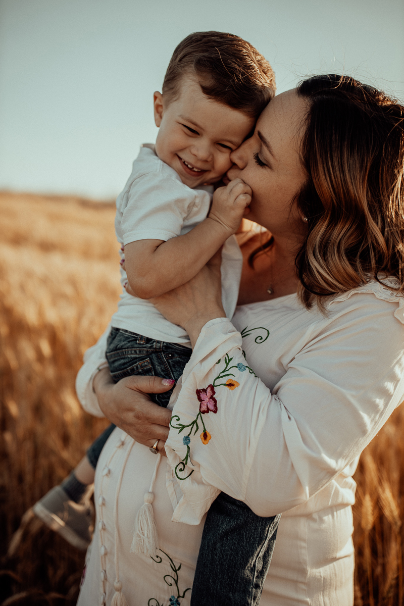 Maternity Photography, mother holding little boy and kissing his cheek