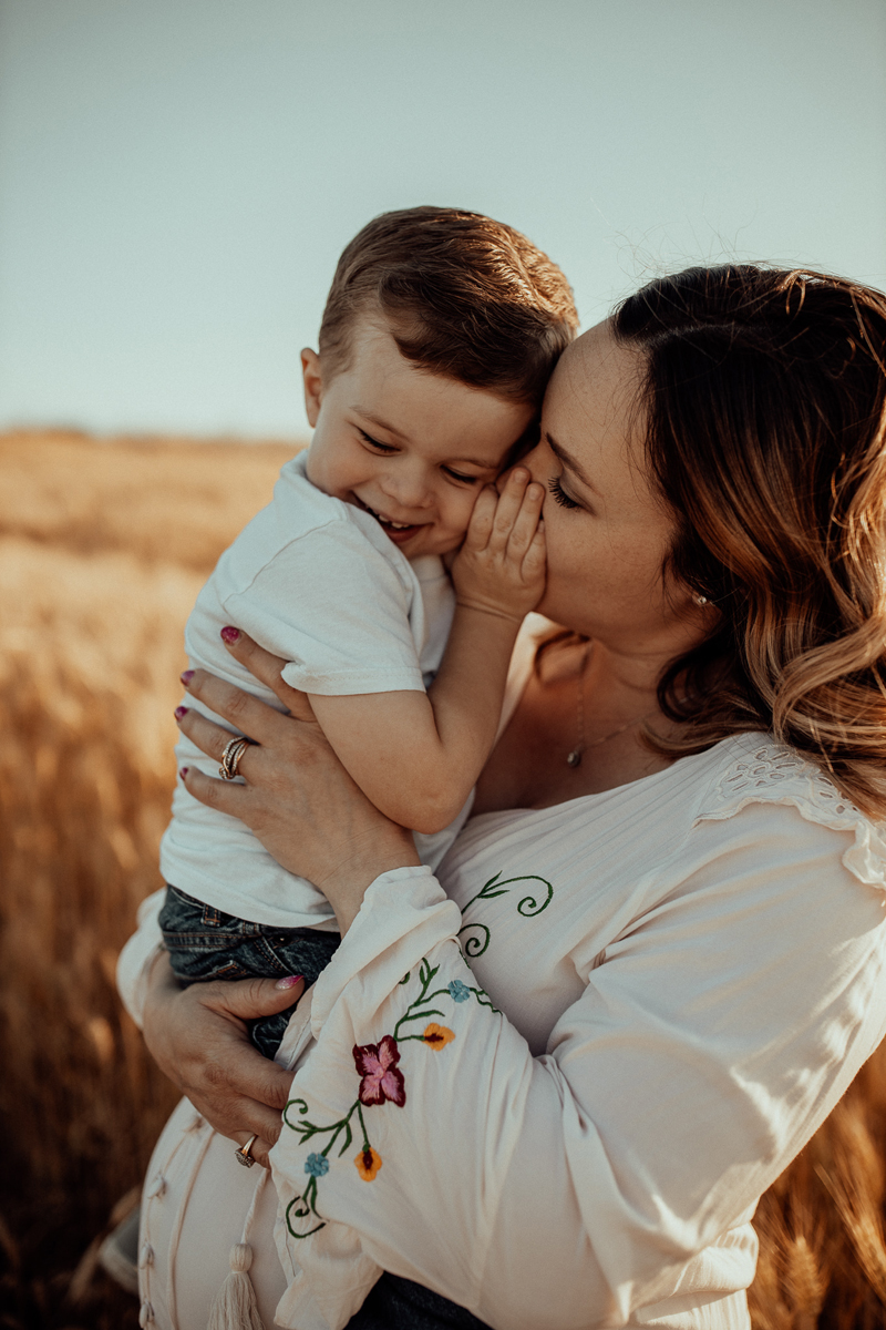 Maternity Photography, mother talking into little boy's ear