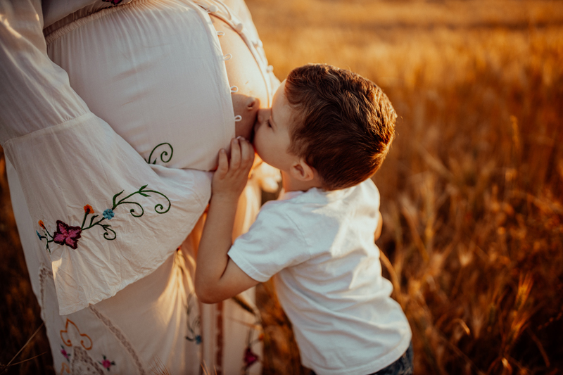 Maternity Photography, little boy kissing mother's belly