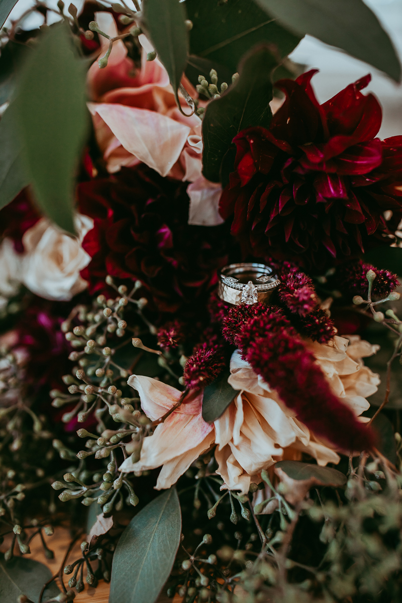 Elopement Photography, rings sitting on dark colored bouquet