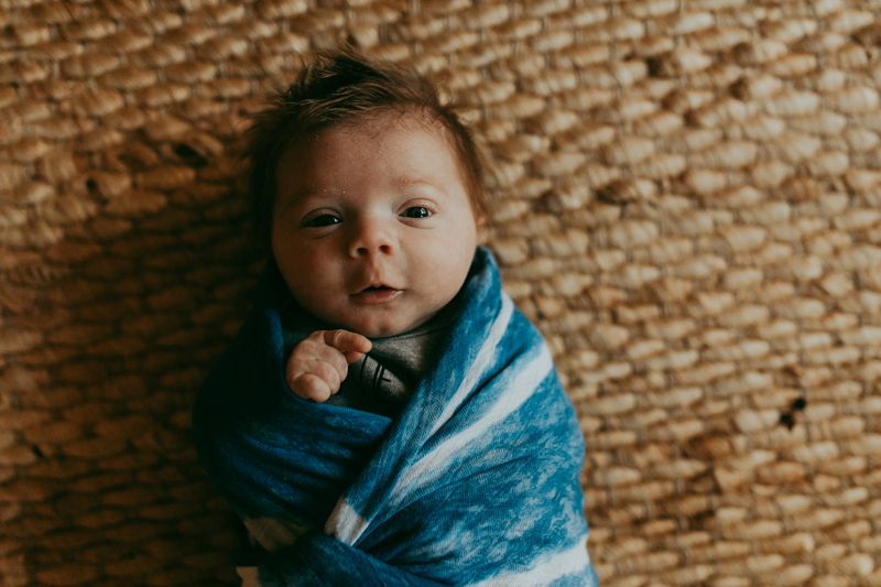 Newborn Photography, baby swaddled in blue and white blanket laying down