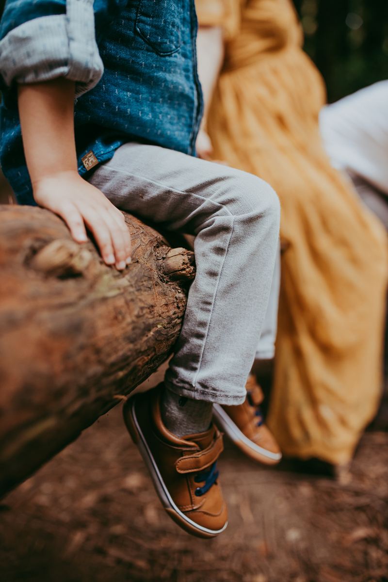 Maternity Photography, detail shot of little boy sitting on a log with mother