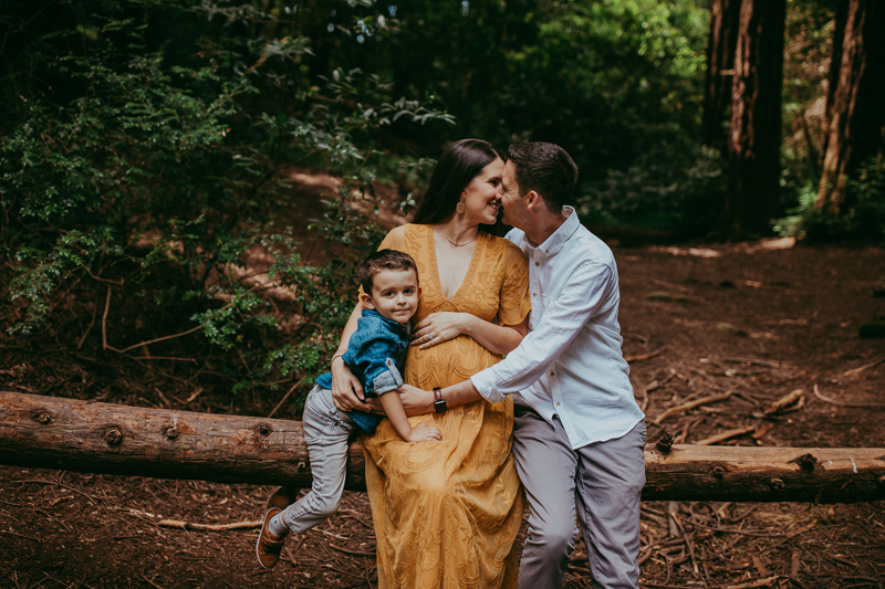 Maternity Photography, family of three sitting on a fallen tree