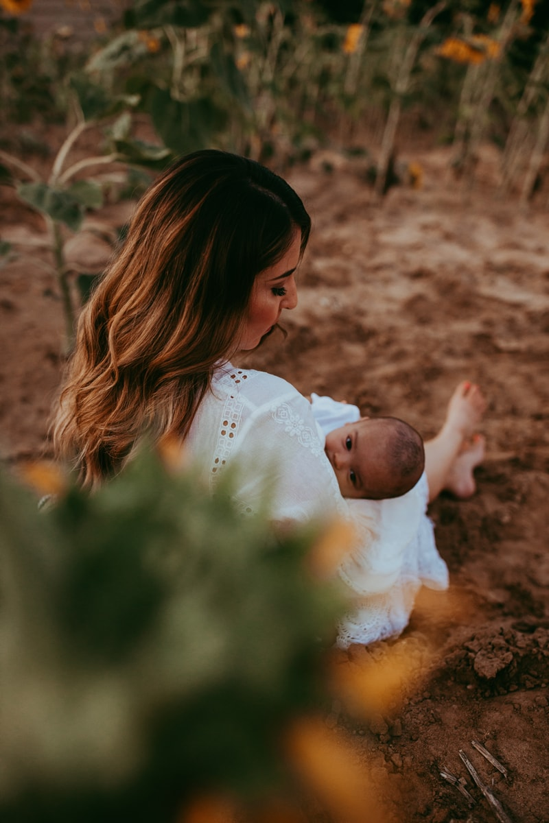 Motherhood Photography, mother breastfeeding baby while sitting in the dirt