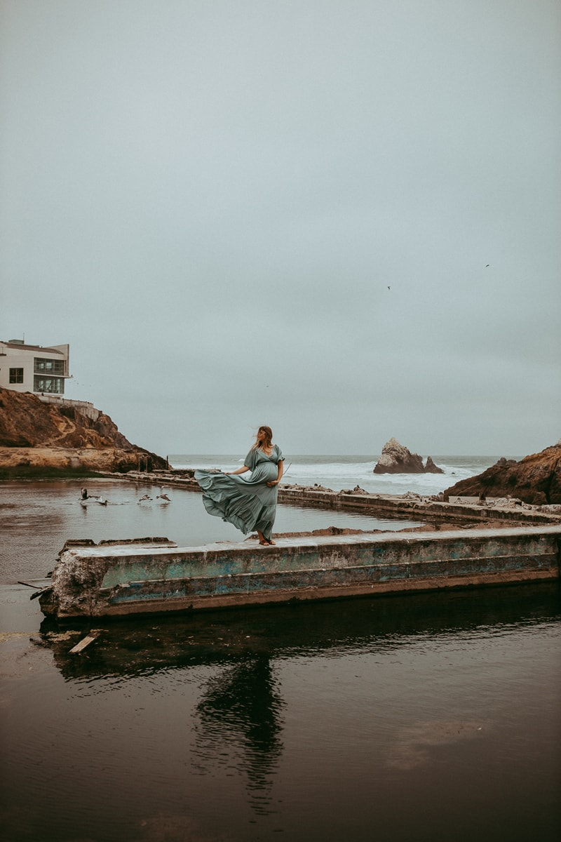 Maternity Photography, wide angle of mother standing on ledge next to water