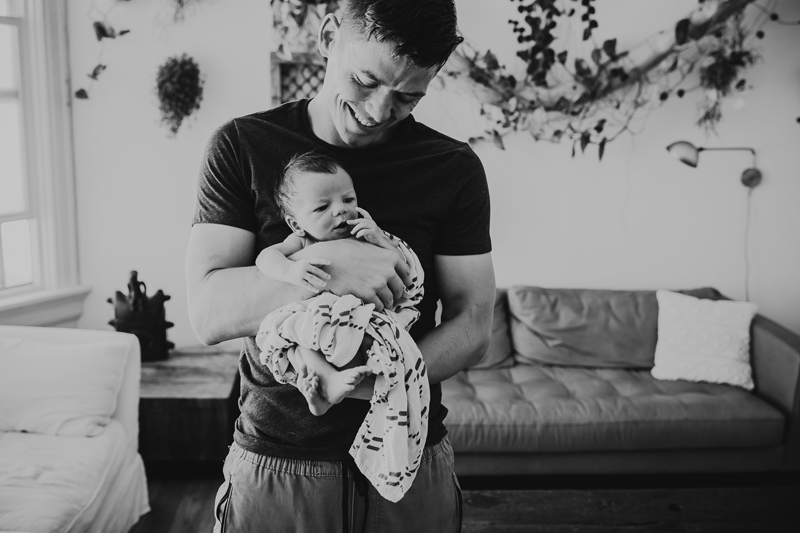 Newborn Photography, black and white of dad holding baby on his chest facing outward