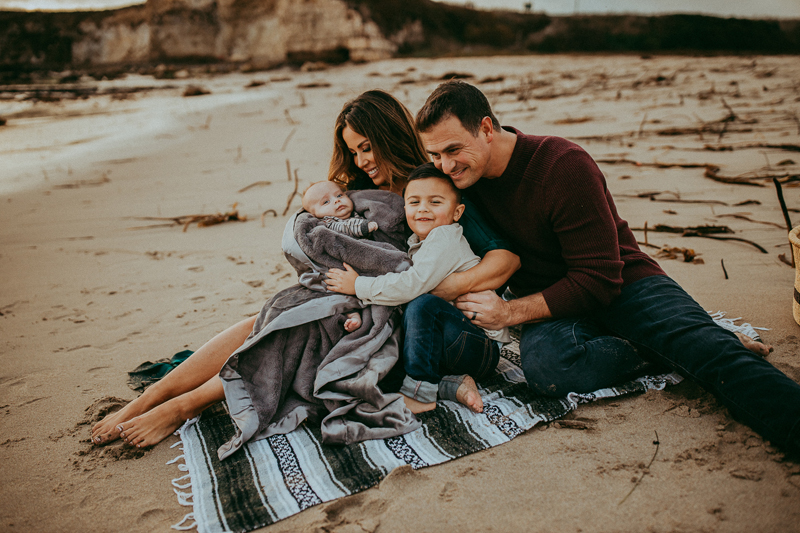 Family Photography, family of 4 sitting together at the beach on a blanket