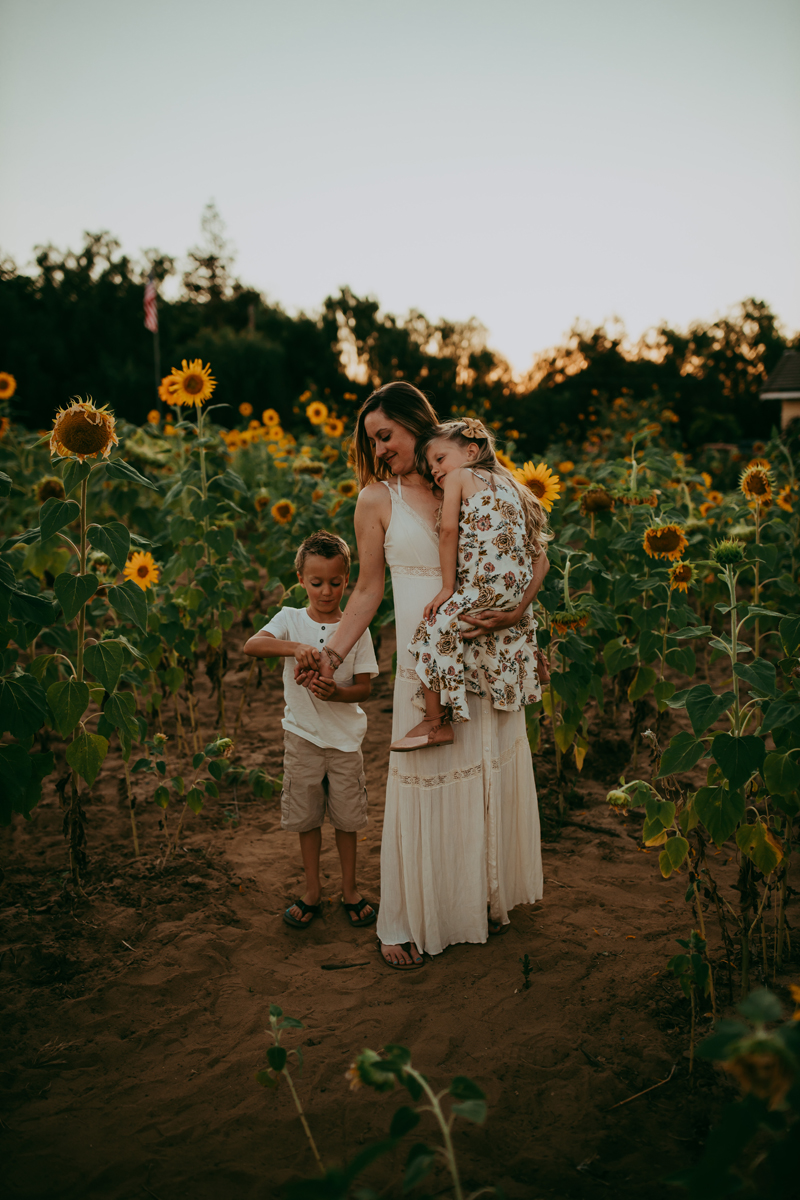 Family Photography, mother and children standing in the sunflower field