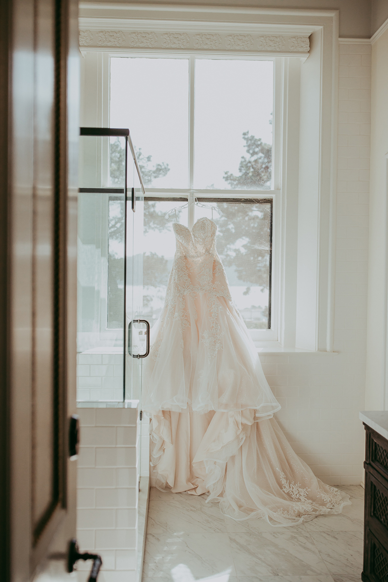 Elopement Photography, bridal gown hanging in white bathroom
