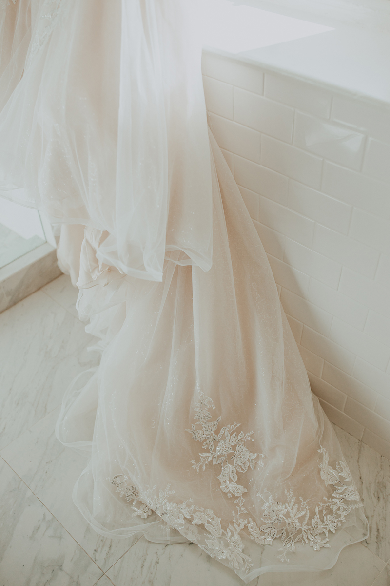 Elopement Photography, detail shot of wedding gown against subway tile