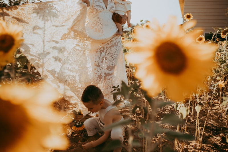 Motherhood Photography, mother and children walking around sunflowers