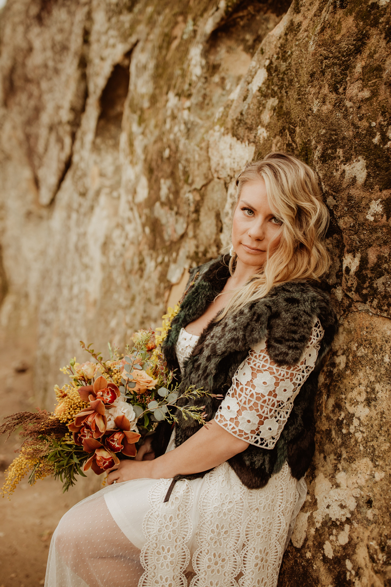 Elopement Photography, bride leaning up against a rock wall