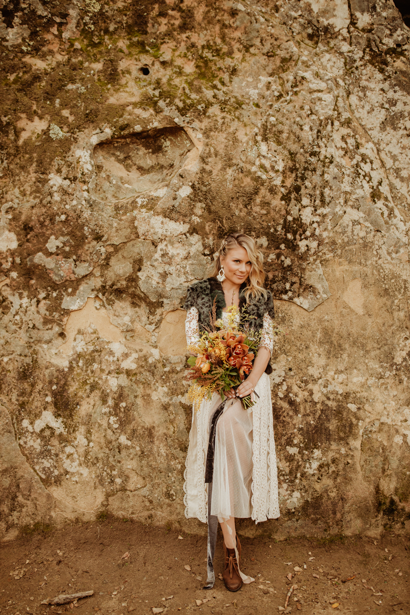 Elopement Photography, bride leaning against a rock wall