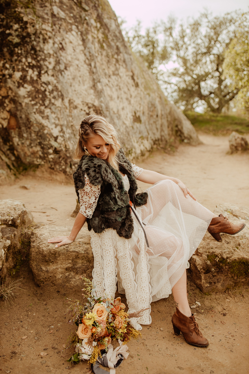 Elopement Photography, bride posing on a rock with bouquet at her feet