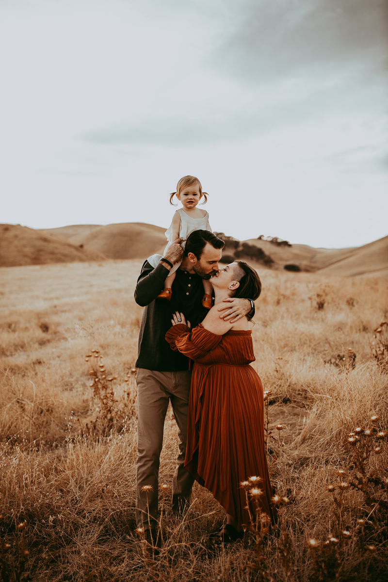 Family Photography, couple kissing with daughter on dad's shoulders