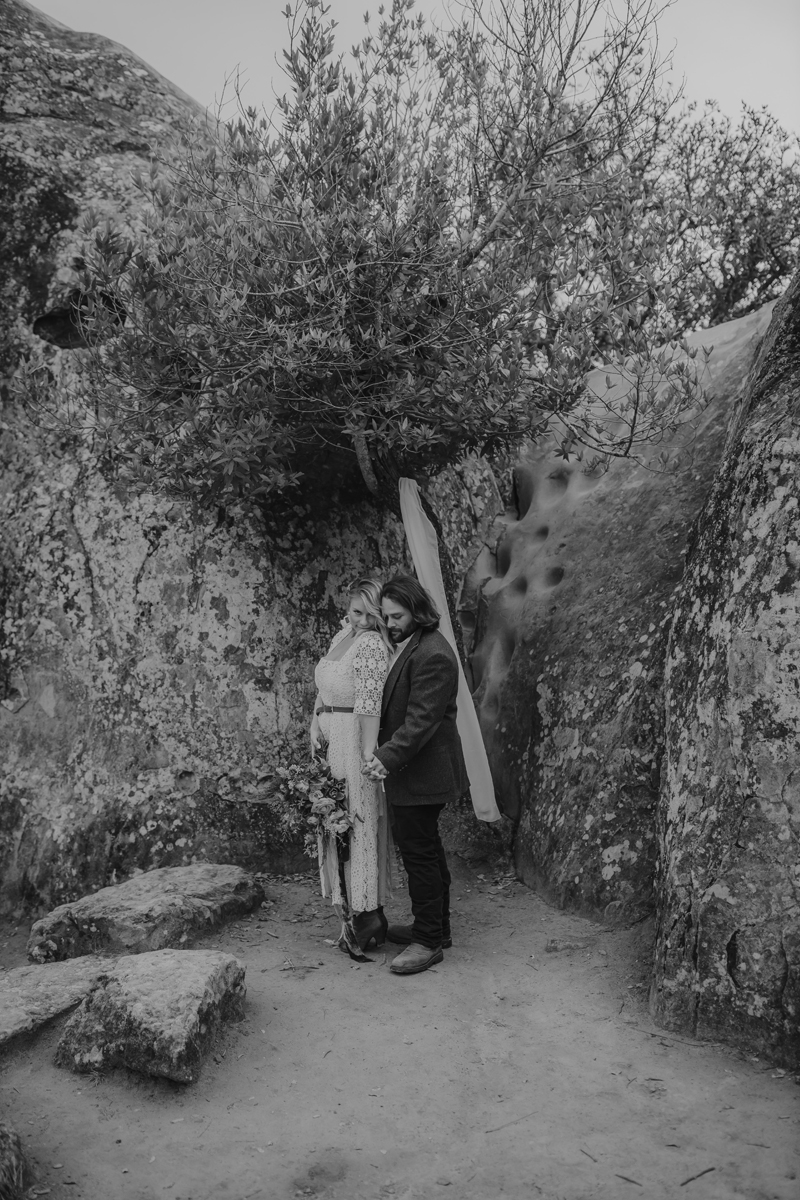 Elopement Photography, black and white image of couple next to large rock formations