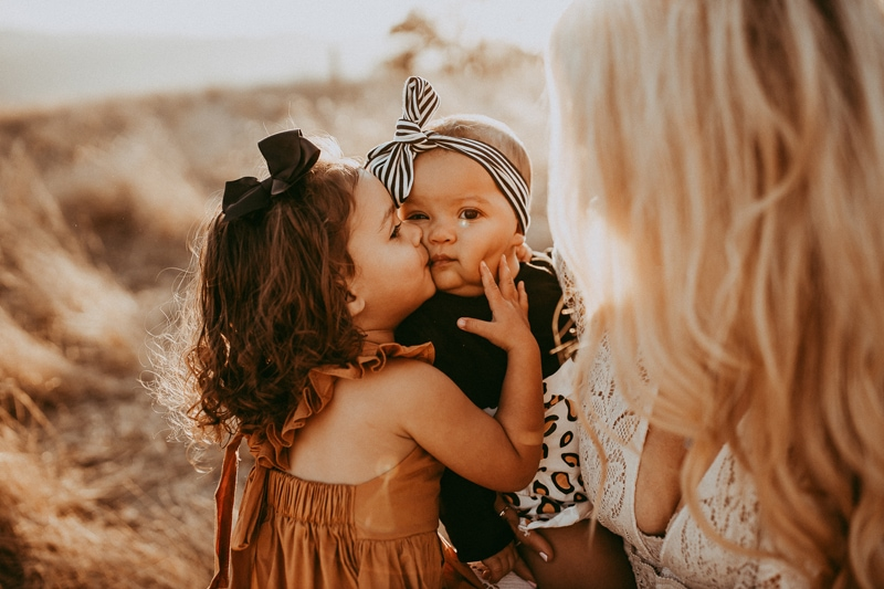 Motherhood Photography, sibling kissing baby sister on the cheek