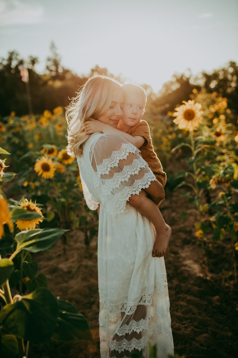 Motherhood Photography, mother and son in sunflower field with sunset in the background