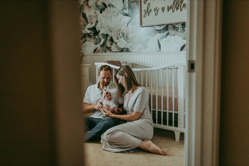 Newborn Photography, looking through nursery door at parents holding newborn baby