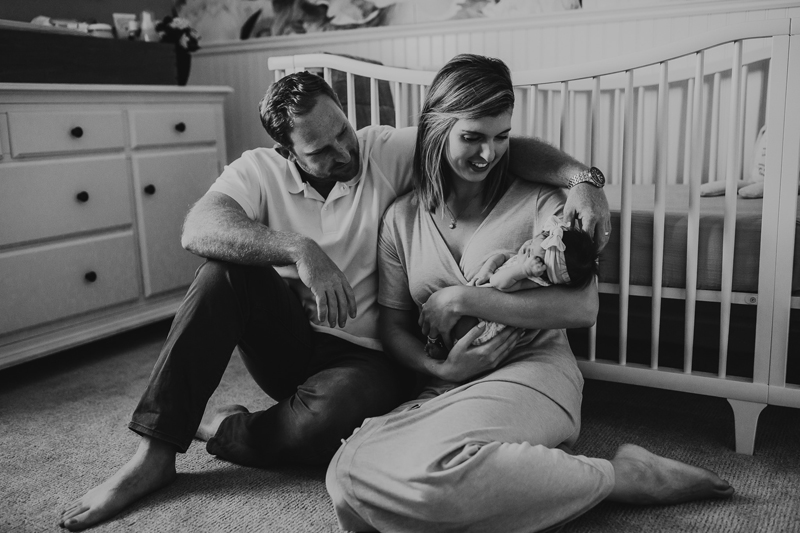 Newborn Photography, black and white image of parents leaning against crib with baby in mother's arms