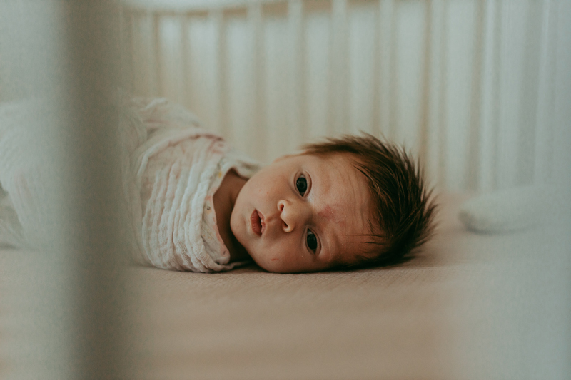 Newborn Photography, baby with lots of hair laying in crib and looking at camera