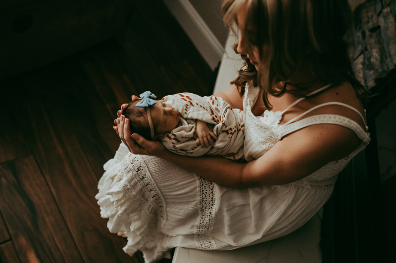 Newborn Photography, mother holding baby on her legs