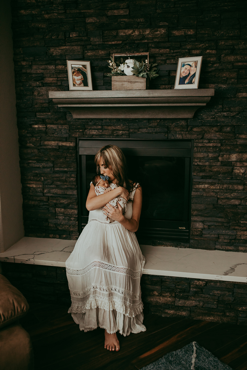 Newborn Photography, mother sitting next to fireplace with baby in her arms
