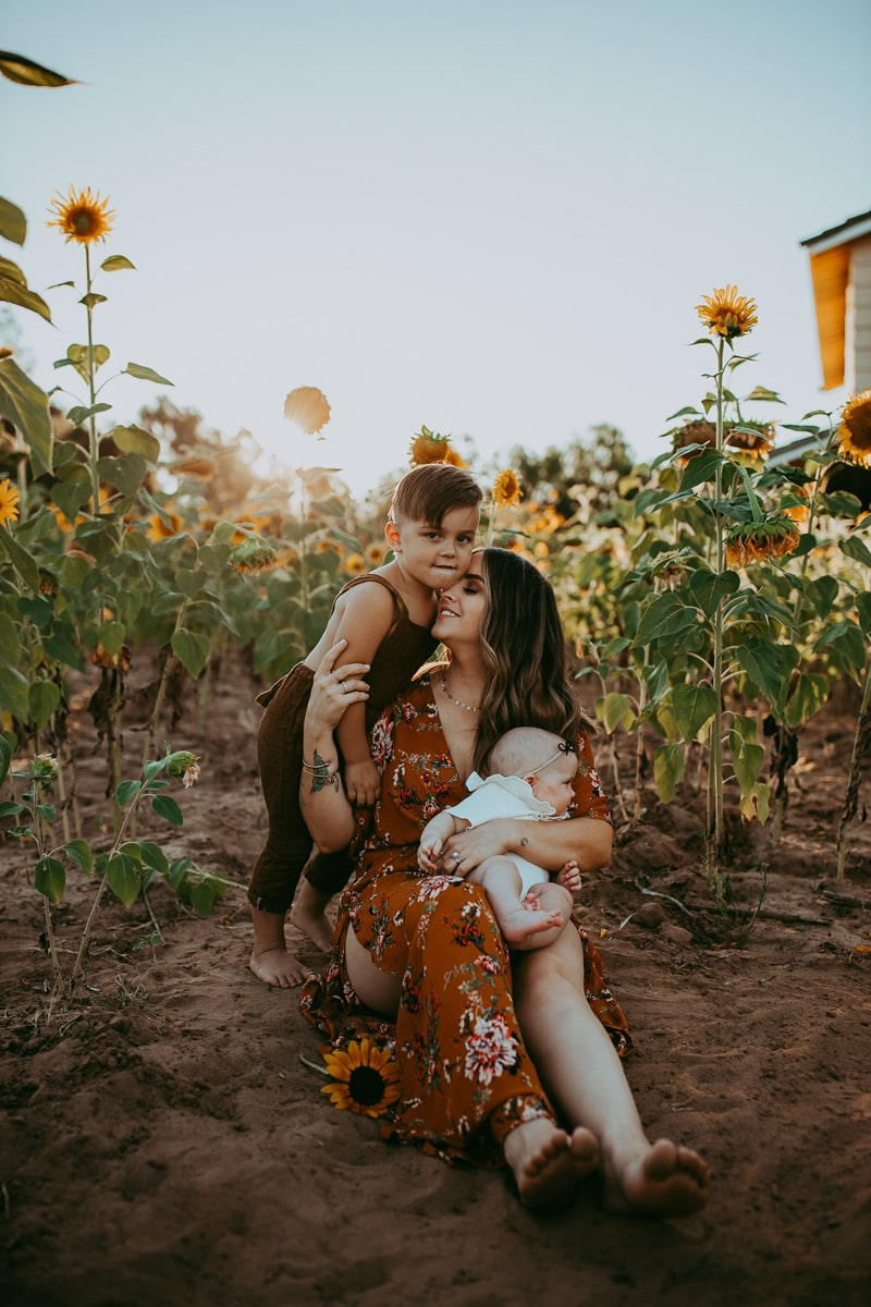 Motherhood Photography, mother sitting in a sunflower field with two children around