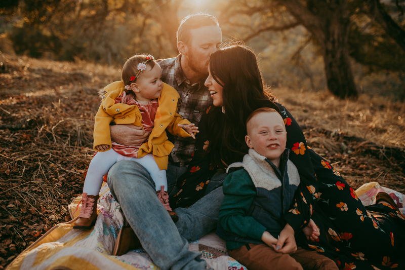 Family Photography, family of four sitting on a blanket on hillside during sunset
