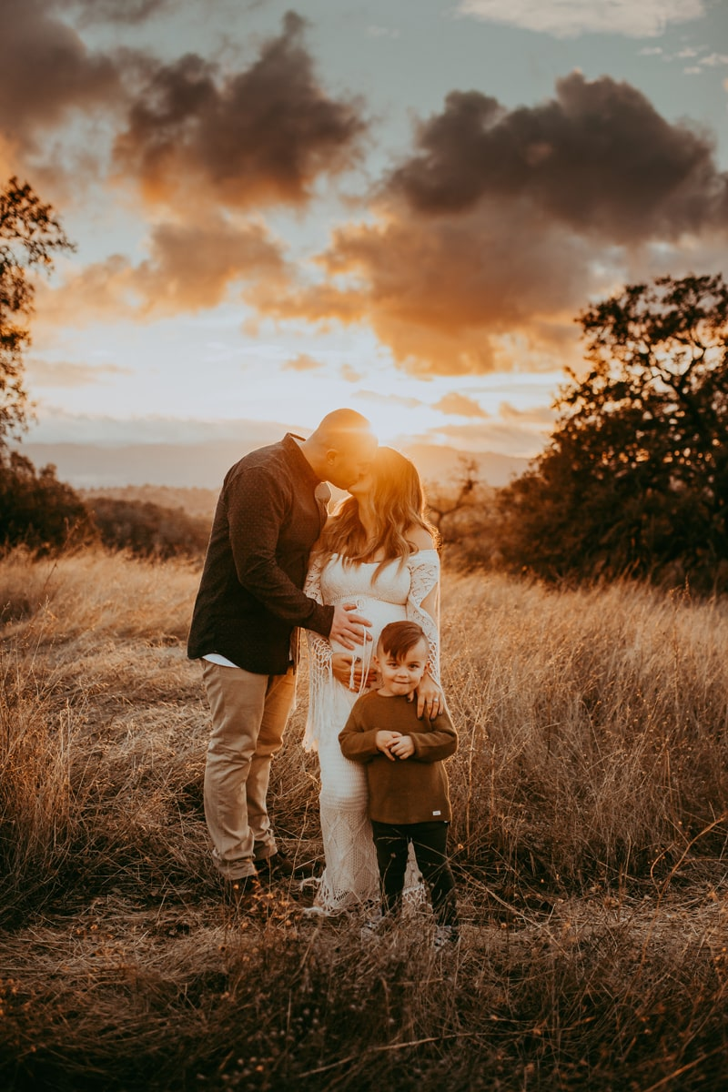 Maternity Photography, family of three standing together in front of sunset