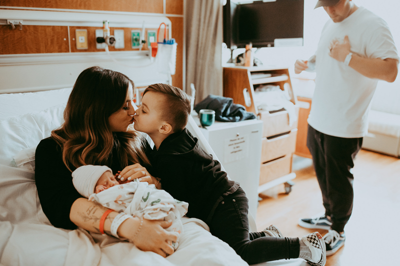 Birth Photography, mother giving older son a kiss with baby in her arms