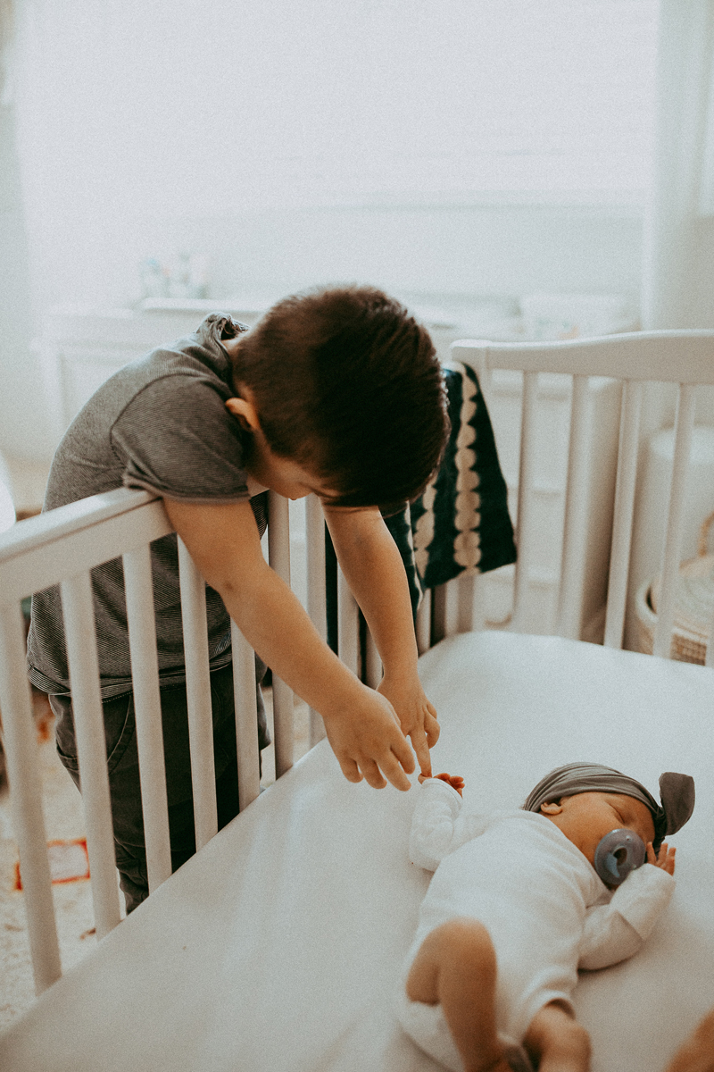 Newborn Photography, brother reaching over crib to touch new baby